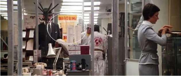Superman II filminden bir kare. Clark Kent yayın yönetmeninin ofisine girmek üzere. Camdaki afişi farkettiniz mi Sarı zeminin üzerinde kırmızı harflerle aynen şöyle yazıyor Daha iyisi olamaz.